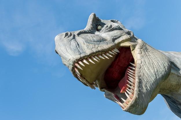 Close-up retrato de dinosaurio tiranosaurio contra el cielo azul