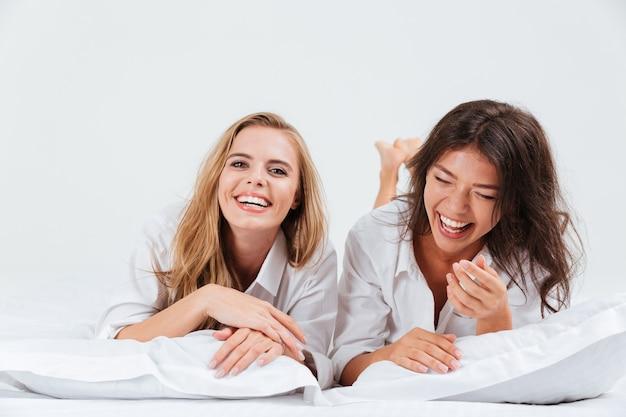 Close up retrato de dos riendo hermosa mujer acostados juntos en la cama con sábanas blancas