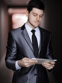 Close up retrato de elegante empresario con tableta digital en el fondo de la oficina