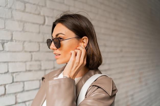 Close up retrato de elegante mujer de pelo corto con auriculares en abrigo de cuero casual y gafas de sol posando sobre pared de ladrillo urbano