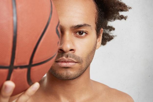 Close up retrato de exitoso jugador de baloncesto tiene bola en primer plano