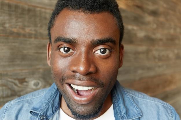 Close up retrato de feliz joven africano masculino vistiendo camiseta blanca y chaqueta de mezclilla con mirada asombrada, posando aislado