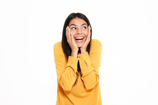 Close-up retrato de feliz mujer morena salida sosteniendo sus mejillas, mirando a un lado