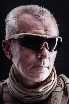Close up retrato de las fuerzas especiales veterano canoso en uniformes de campo, negro