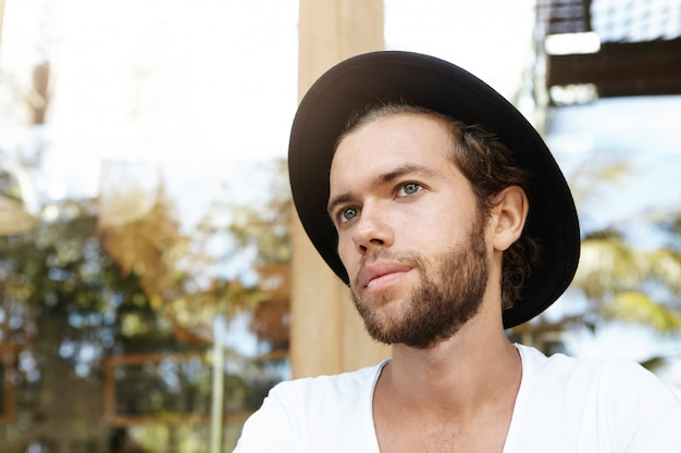 Close up retrato de guapo joven inconformista caucásico con barba espesa con sombrero negro y camiseta blanca con aspecto triste o cansado