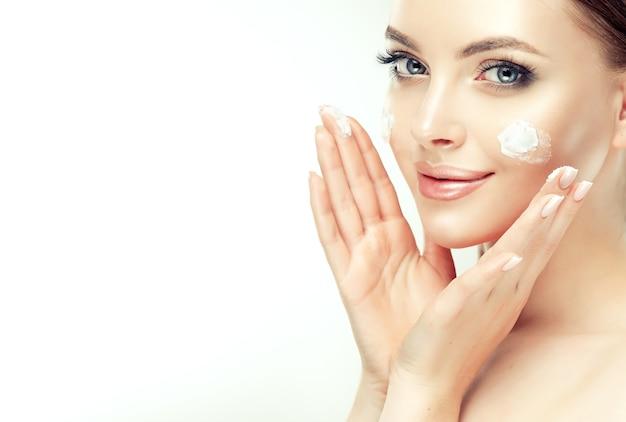 Close up retrato de hermosa, joven, mujer de cabello castaño con manchas de crema cosmética