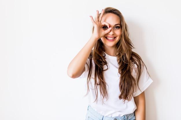 Close up retrato de hermosa mujer caucásica rubia alegre sonriendo, mostrando dientes blancos, mirando a la cámara a través de los dedos en gesto bien. expresiones faciales, emociones y lenguaje corporal.