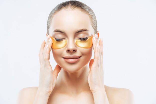 Close up retrato de hermosa mujer europea sonriente cierra los ojos, disfruta de la terapia ocular antienvejecimiento, aplica parches dorados, tiene la piel limpia y fresca, se para sin camisa contra el fondo blanco. tratamiento facial