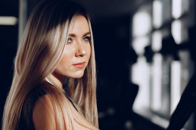 Close up retrato de una hermosa mujer rubia con cabello largo sonriendo