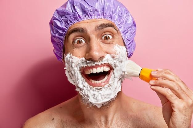 Close up retrato de hombre alegre tiene rutina matutina, aplica gel de afeitar en la cara, sonríe ampliamente, está de buen humor