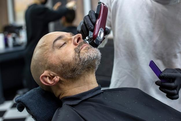 Close up retrato de un hombre barbudo en peluquería durante el corte de barba