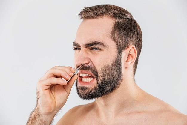 Close up retrato de un hombre barbudo que sufre de pie aislado sobre blanco, arrancando el pelo de la nariz