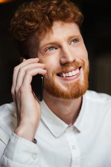 Close-up retrato de hombre guapo con barba pelirroja sonriente en camisa blanca tocando en el teléfono móvil