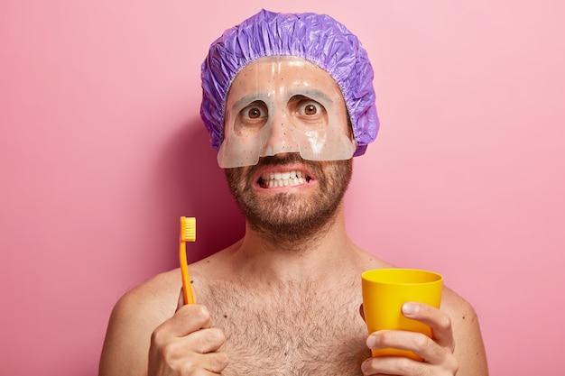 Close up retrato de hombre guapo sostiene cepillo de dientes y taza amarilla, se para con shouders desnudos, tiene máscara en la cara