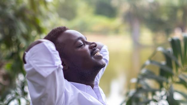 Close up retrato de hombre de negocios africano con cara tranquila ojos cerrados de pie en la naturaleza verde con las manos sobre la cabeza