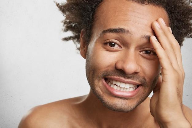 Close up retrato de hombre de piel oscura rastrojo desnudo, mantiene la mano en la cabeza