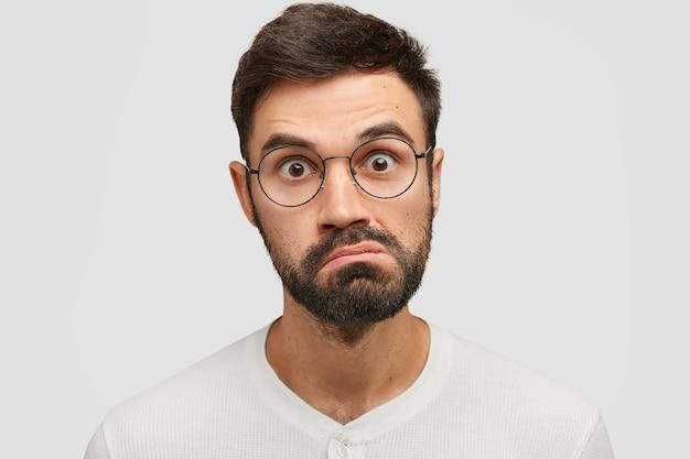 Close up retrato de hombre sorprendido enojado guapo mira con desconcierto, frunce los labios y mira fijamente