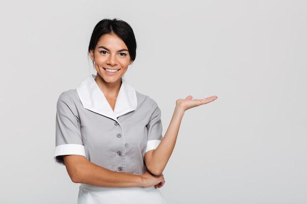 Close-up retrato de joven ama de casa feliz en uniforme mostrando la palma vacía