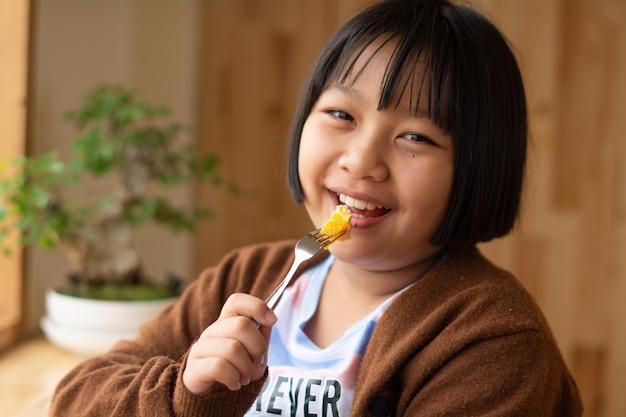 Close up retrato de joven asiática comiendo fruta pequeña con un tenedor