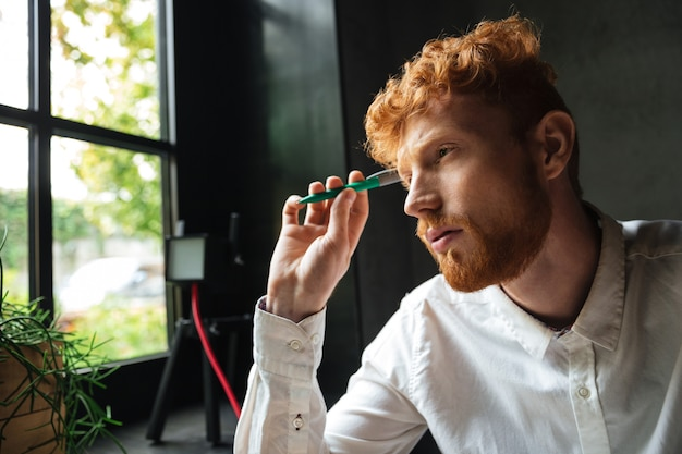 Close-up retrato de joven barbudo concentrado hombre barbudo, sosteniendo la pluma verde, mirando a la ventana