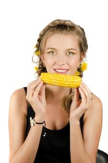 Close-up retrato de joven belleza mujer comiendo mazorcas de maíz en un blanco