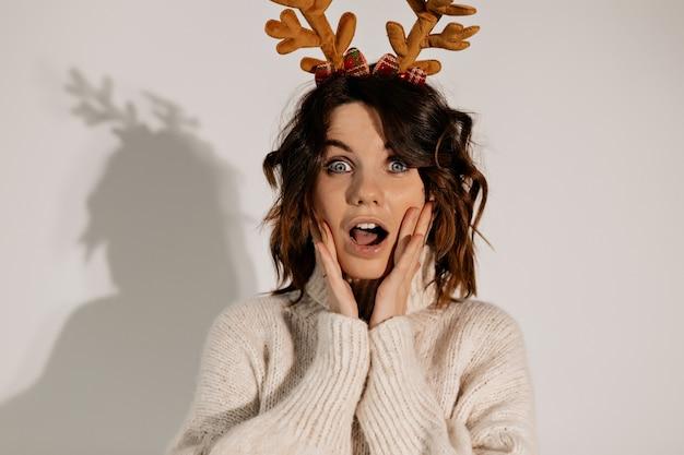 Close up retrato de joven bonita posando con emociones sorprendidas tocando la cara con las manos vestidas con suéter de punto y tocados de navidad