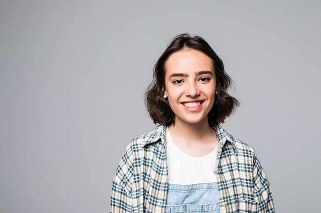 Close up retrato de joven hermosa alegre con cabello largo oscuro en camisa gris casual sonriendo con dientes, mirando