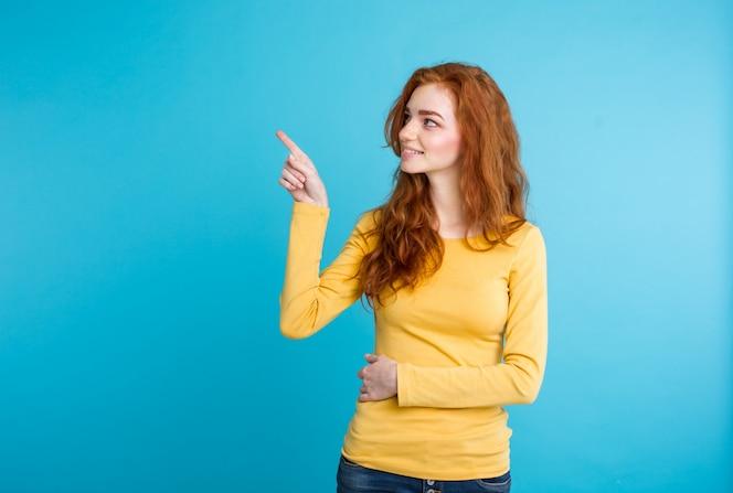 Close up retrato joven hermosa atractiva redhair niña feliz con algo y señalando el dedo. fondo de pastel azul. copie el espacio.