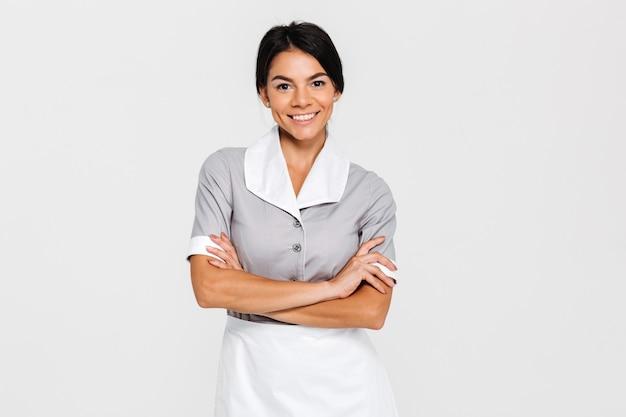 Close-up retrato de joven sonriente ama de llaves en uniforme de pie con las manos cruzadas