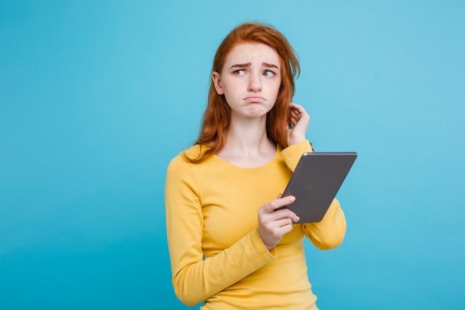 Close up retrato joven y bella atractiva licitación ginger redhair niña feliz sonriendo en la mesa digital con wining algo. fondo de pastel azul. copie el espacio.