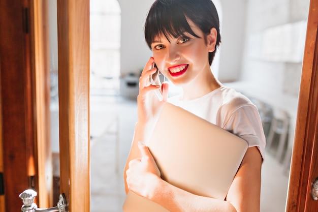 Close-up retrato de linda chica de pelo negro hablando por teléfono y sosteniendo la computadora