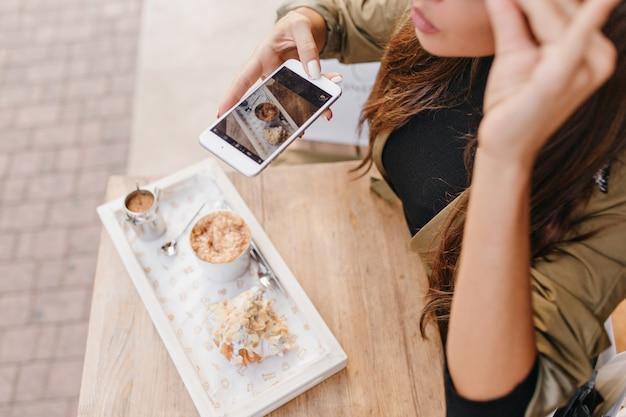 Close-up retrato de modelo femenino bronceado haciendo foto de su postre en la cafetería al aire libre