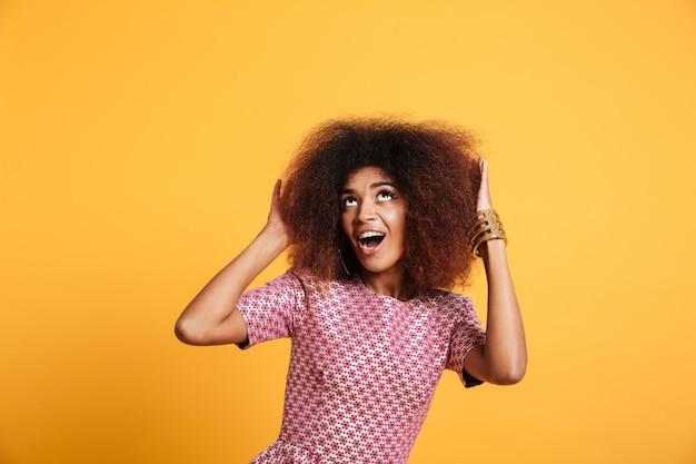 Close-up retrato de mujer africana asombrada en vestido tocando su peinado afro, mirando hacia arriba