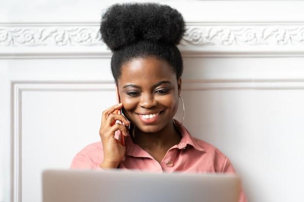 Close up retrato de mujer afroamericana con peinado afro en camisa rosa sonriendo, hablando por teléfono