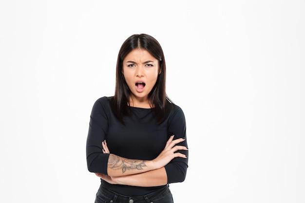Close-up retrato de mujer asiática enojada gritando y de pie con las manos cruzadas