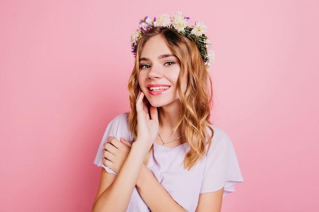 Close-up retrato de mujer blanca guapa en diadema de flores sonriendo a la cámara