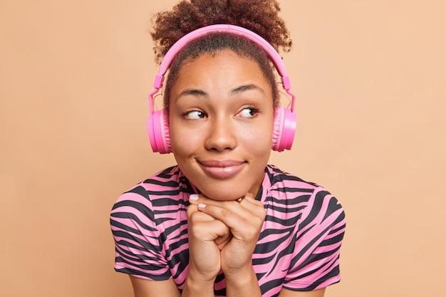 Close up retrato de mujer contenta pensativa mantiene las manos debajo de la barbilla usa auriculares en las orejas escucha pista de audio o conferencia tutorial concentrada a un lado aislado sobre pared beige