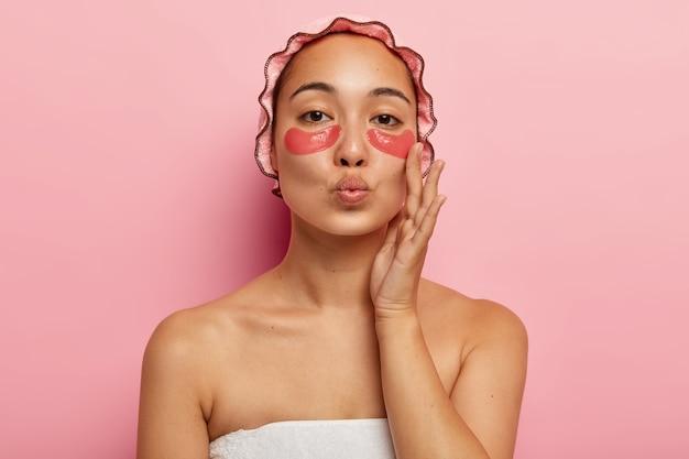 Close up retrato de mujer encantadora tiene belleza natural, mantiene los labios doblados para besar a alguien, usa gorro de baño impermeable, toca la mejilla, disfruta de la frescura de la piel, tiene parches en los ojos en la cara, posa en interiores