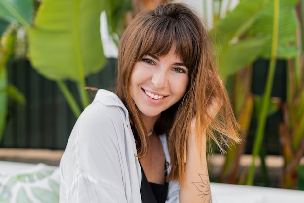 Close up retrato de mujer europea sonriente posando sobre jardín tropical