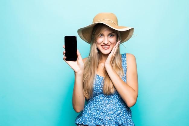 Close up retrato de una mujer joven alegre en vestido y sombrero de verano que muestra el teléfono móvil de pantalla en blanco aislado sobre fondo azul.