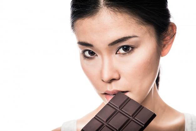 Close-up retrato de mujer joven con barra de chocolate con leche