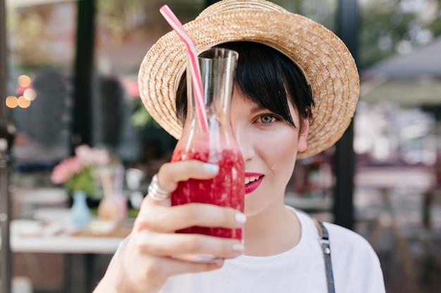 Close-up retrato de mujer joven elegante con pelo corto negro y piel pálida sosteniendo un vaso de limonada helada