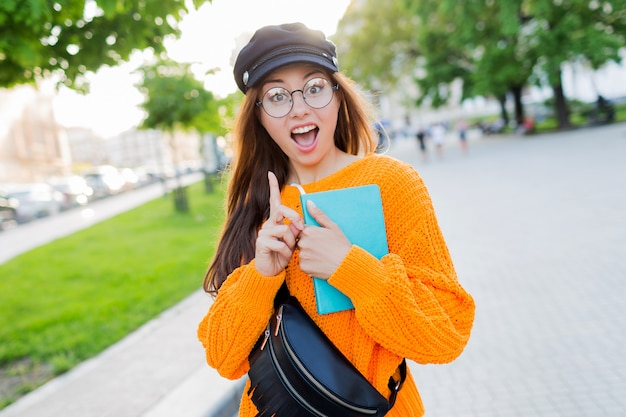 Close-up retrato de mujer joven encantadora sorprendida señalando con el dedo