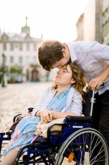 Close-up retrato de mujer joven feliz en silla de ruedas y su esposo besando su frente, caminando al aire libre en la ciudad vieja