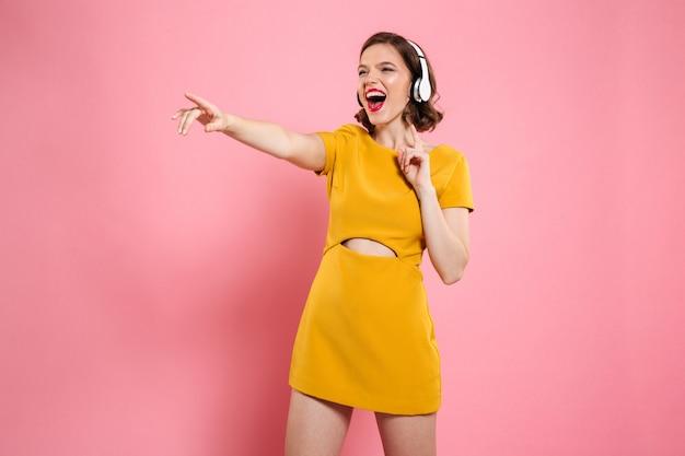 Close-up retrato de mujer joven feliz en vestido amarillo y auriculares apuntando con el dedo, mirando a un lado