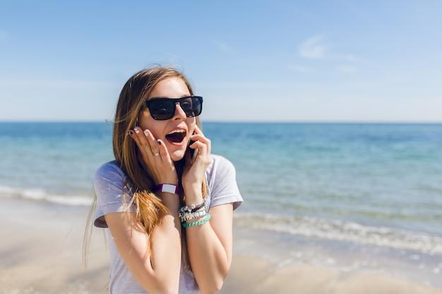 Close-up retrato de mujer joven con pelo largo de pie cerca del mar azul