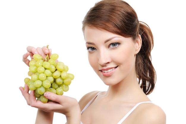 Close-up retrato de mujer joven con racimo de uvas