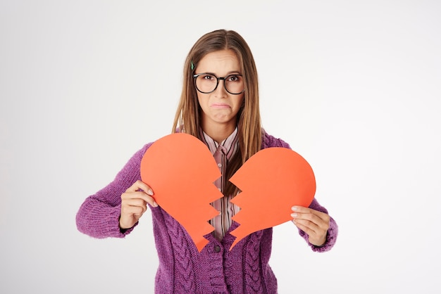Close up retrato de mujer joven sosteniendo una forma de corazón roto