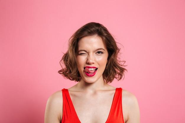 Close-up retrato de mujer muy juguetona guiña un ojo, mostrando la lengua, aislado en rosa
