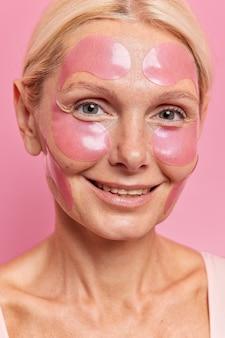 Close up retrato de mujer rubia de mediana edad sonríe aplica suavemente parches de hidrogel